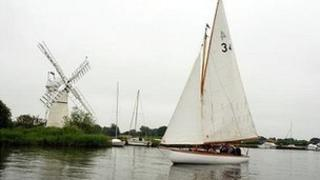 Sailing boat on the Norfolk Broads, with the Thurne windmill in the background