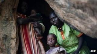A mother in the Nuba mountains of South Kordofan shelters in a cave with her children [1 July 2011]