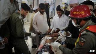 Pakistani paramedics treat an injured suicide attack victim at a hospital in Peshawar on March 11, 2012.
