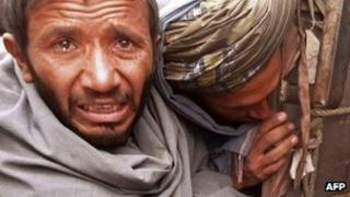 A mourner cries over the bodies of Afghan civilians, allegedly shot by a rogue US soldier in Alkozai village.
