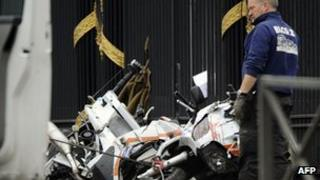 A man stands beside one of the badly damaged motorcycles outside the Royal Palace in Brussels, Belgium
