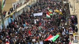 Syrians, some holding up the Kurdish flag, at a protest in Qamishli, Syria on 12 March