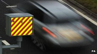 A sharp picture of a speed camera box with a blurry image of a car speeding past.