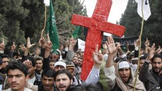 Protesters carrying a red cross fill a street in the village of Panjwai, Afghanistan [13 March 2012]