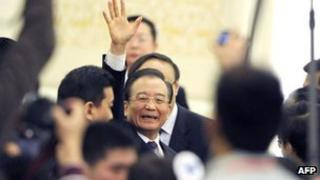 Wen Jiabao waves to media as he leaves after the press conference in Beijing, 14 March 2012
