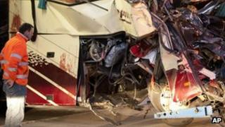 A rescue worker looks at blood stains on the wreckage of a tourist bus from Belgium (14 March 2012)