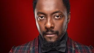 Will.I.Am in a publicity photograph for BBC's The Voice. He is wearing a smart black bowtie and a quirky, tartan dinner jacket.