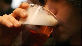 man drinks pint