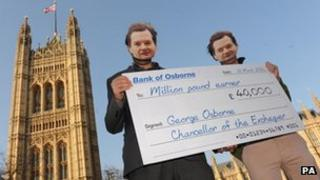 Protesters highlight Chancellor George Osborne's reduction in income tax for high earners