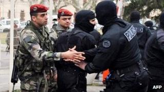 A masked member of France's RAID police commandos shakes hands with a paratrooper at Perignon barracks after the end of the siege in Toulouse, 22 March