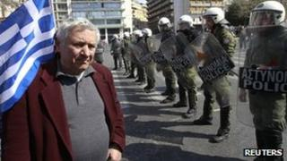 A man stands in front of a police formation during a military parade marking Greece's Independence Day in Athens