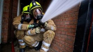 Firefighters spraying hose