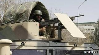 An Afghan National Army soldier keeps watch at the site of motorcycle bomb attack in Kandahar province March 14, 2012.