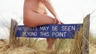 A sign at a nudist beach