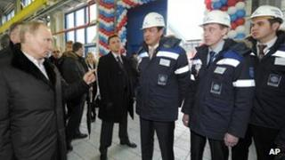 Vladimir Putin speaks with workers as he visits an oil terminal at the Ust-Luga port March 23, 2012.