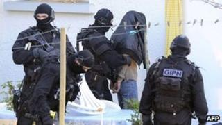 Policemen arrest a man in Coueron, western France, on March 30, 2012 as part of down raids in several French cities.