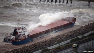 Cargo ship hit a rock in rough seas off the north Wales coast.
