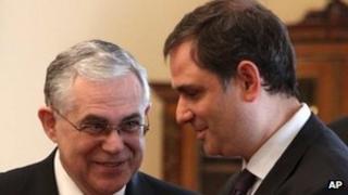 Greek Prime Minister Lucas Papademos, left, speaks with the new Greek Finance Minister Philippos Sachinidis