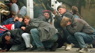 People shelter from Serb sniper in Sarajevo, 1992