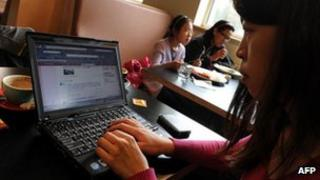 A woman views the Chinese social media website Weibo at a cafe in Beijing, 2 April 2012