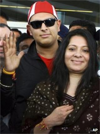Indian cricket star Yuvraj Singh gestures as he stands with his mother Shabnam as they make their way through the media on arrival at the airport in New Delhi, India, Monday, April 9, 20