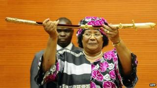 The President of Malawi, Joyce Banda, holds a ceremonial sword as she is sworn in