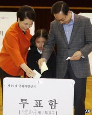 South Korean President Lee Myung-bak, right, and his wife Kim Yoon-ok cast their ballots in the parliamentary elections as their unidentified granddaughter looks on at a polling station in Seoul, South Korea, on 11 April, 2012