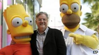 Matt Groening, creator of The Simpsons, stands between Bart and Homer Simpson in a file picture 14 February 2012