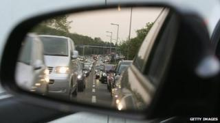Traffic seen is car's wing mirror