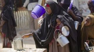 A woman collects food at a camp for those displaced by the famine or conflict in Somalia