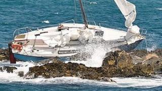 Yacht stuck on rocks outside St Peter Port Harbour