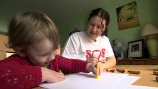 Toddler drawing with mum watching in the background