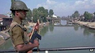 An Indian paramilitary soldier stands guard on a bridge on the Jhelum river in central Srinagar.