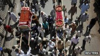 Relatives and residents carry the caskets of men who were killed in the Boeing 737 airliner crash in Islamabad on Friday, during their funeral in Karachi April 22, 2012.