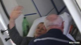 Yulia Tymoshenko waves from a stretcher as she is moved to an ambulance in Kharkiv, 22 April
