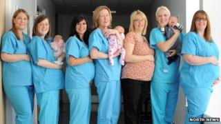 Seven midwives pose with bumps and babies