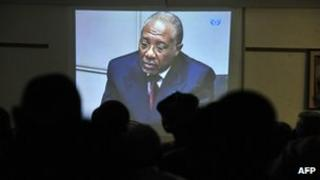 People watch the trial of Liberian ex-leader Charles Taylor (on screen) taking place in the Hague, inside the Special Court in Freetown, Sierra Leone on Friday