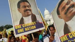 Sri Lankans carry posters of President Mahinda Rajapaksa at a rally opposing the UN Human Rights Council vote against the country - 22 March 2012