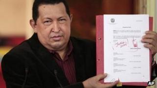 Venezuela President Hugo Chavez holds up copy of new labour law on 30 April 2012