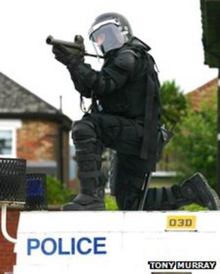 Police officer with baton round gun