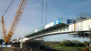 The first section of the new bridge is lifted into place