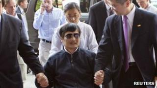A handout photo from US Embassy Beijing Press office shows blind activist Chen Guangcheng (2nd L) sitting in a wheelchair as he is accompanied by U.S. Ambassador to China Gary Locke (2nd R) at a hospital in Beijing, May 2, 2012.