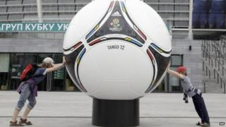 Kids try and push a model of an official Euro 2012 ball