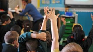Child's hand raised in classroom