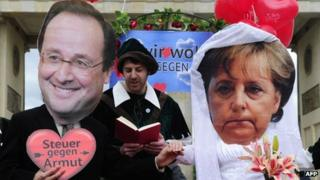 Activists wearing masks of Francois Hollande and Angela Merkel taking part in a fake marriage in Berlin, 7 May 2012