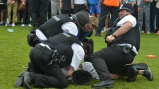 Police arrest a teenager at the match