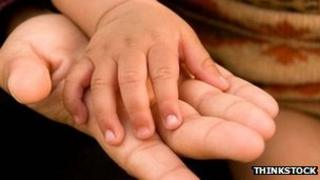 A baby's hand rests on a woman's hand