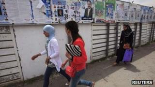 Women walk past electoral posters in Algiers May 9, 2012.