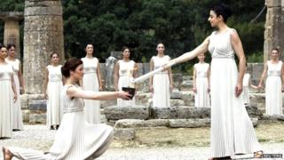 The Olympic flame is lit in a ceremony in Greece by actresses dressed in white robes.