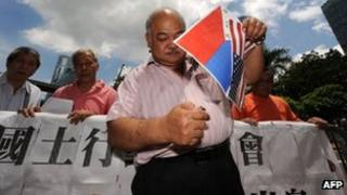 Protester Tsang Kin-shing, who supports Chinese sovereignty over the Scarborough Shoal, prepares to burn a paper Philippine and a US flag during a protest at the Philippine consulate